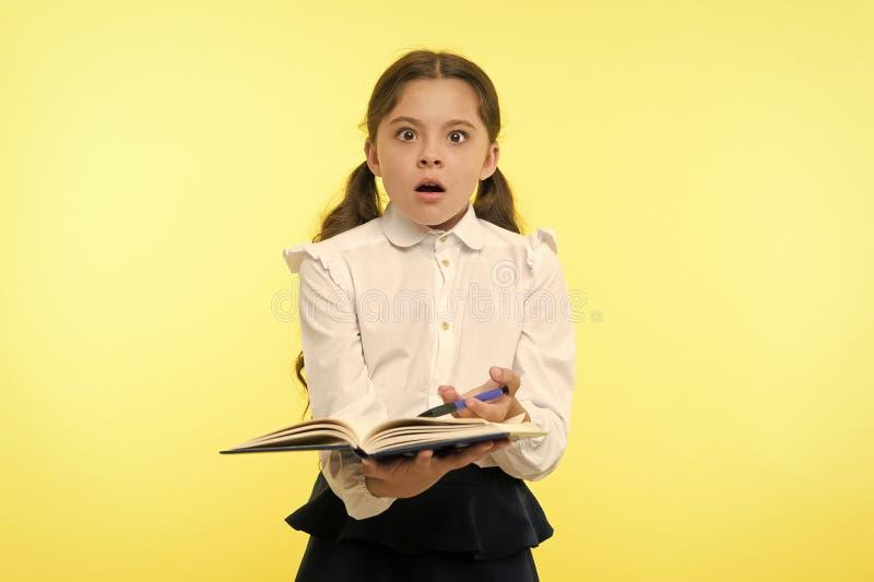 Χαριτωμένη μαθήτρια κοριτσιών στο ομοιόμορφο βιβλίο λαβής με το κίτρινο υπόβαθρο πληροφοριών Ο μαθητής παίρνει τις πληροφορίες απ στοκ εικόνες