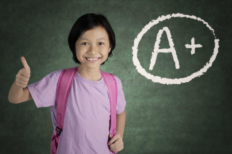 Χαριτωμένη μαθήτρια που παίρνει το βαθμό Α συν στοκ εικόνες