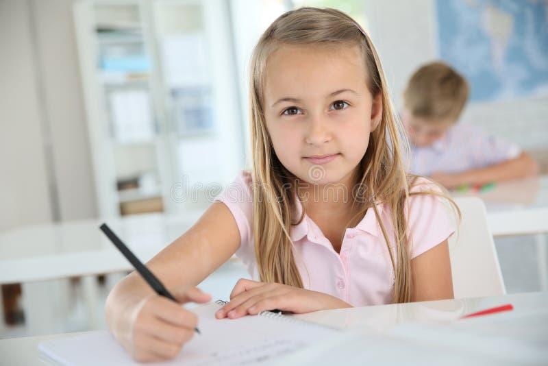 Χαριτωμένη μαθήτρια wiritng κάτω από τις σημειώσεις στοκ εικόνα