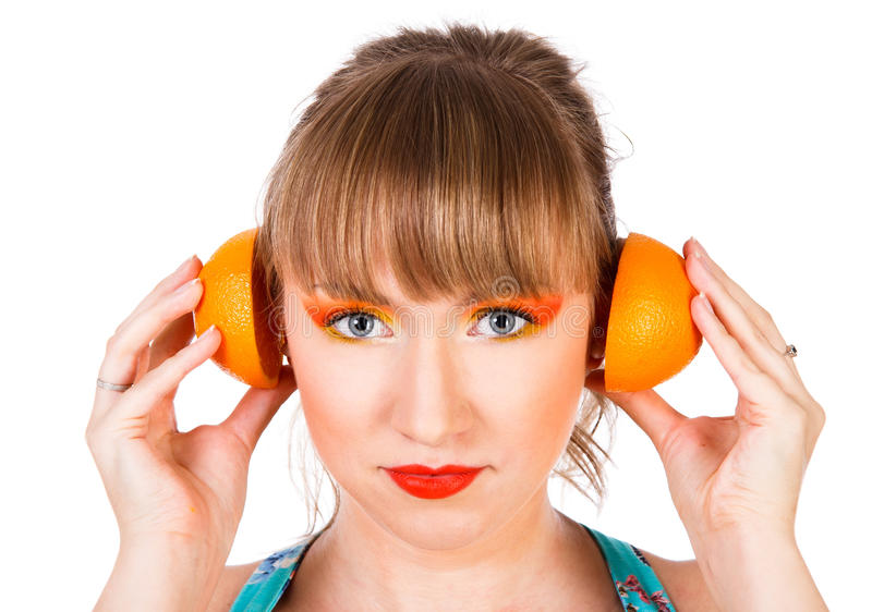 Χαριτωμένη νέα γυναίκα με μισά των πορτοκαλιών φρούτων κοντά στα αυτιά της στοκ φωτογραφίες