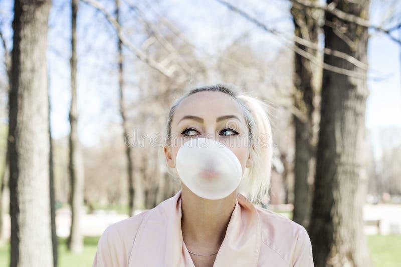 Χαριτωμένη νέα γυναίκα με την τσίχλα φυσαλίδων υπαίθρια στοκ εικόνα με δικαίωμα ελεύθερης χρήσης