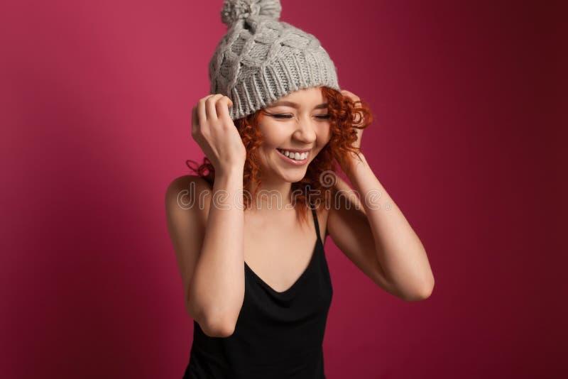 Χαριτωμένη νέα γυναίκα που φορά τη θερμή τοποθέτηση χειμερινών καπέλων στο στούντιο στοκ εικόνα