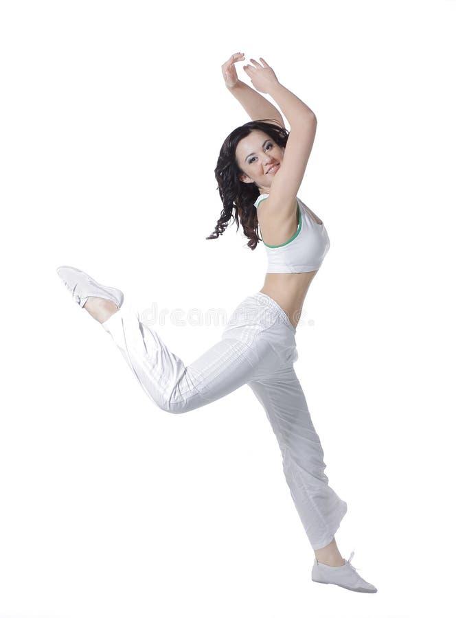 Χαριτωμένη νέα γυναίκα που χορεύει ευτυχώς Φωτογραφία στην άσπρη ανασκόπηση στοκ φωτογραφία