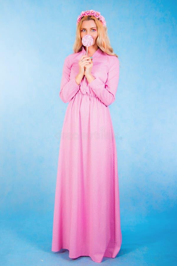 Χαριτωμένη νέα γυναίκα σε ένα μακρύ ρόδινο φόρεμα που κρατά μια καραμέλα στοκ εικόνα με δικαίωμα ελεύθερης χρήσης