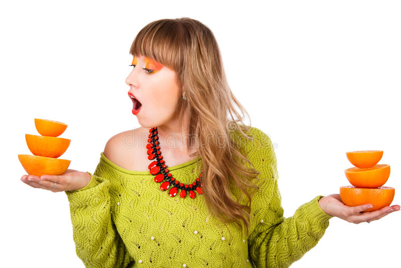Χαριτωμένη νέα γυναίκα σε ένα πράσινο πουλόβερ με δύο πυραμίδες του πορτοκαλιού στοκ εικόνες
