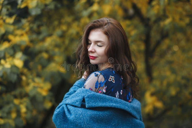 Χαριτωμένη νέα γυναίκα στο μπλε παλτό και το μπλε φόρεμα που απολαμβάνει τη φύση στο πάρκο φθινοπώρου Όμορφη κάλυψη υποβάθρου κίτ στοκ εικόνες