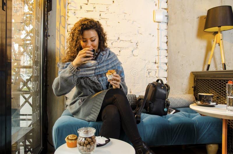 Χαριτωμένη νέα ενήλικη γυναίκα που τρώει τα γλυκά και που πίνει τον καφέ στοκ εικόνες