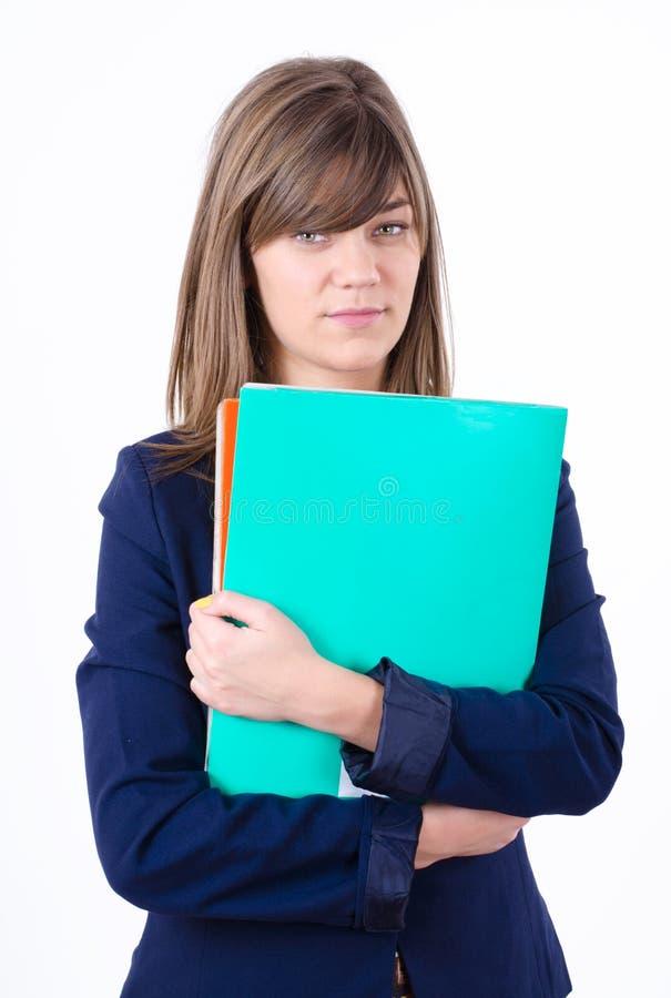 Χαριτωμένη νέα επιχειρησιακή γυναίκα σε ένα σακάκι με τις πράσινες και πορτοκαλιές γραμματοθήκες στα χέρια που φαίνονται άμεσα προ στοκ φωτογραφία με δικαίωμα ελεύθερης χρήσης