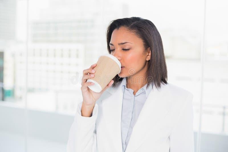 Χαριτωμένη νέα μελαχροινή μαλλιαρή επιχειρηματίας που απολαμβάνει τον καφέ στοκ εικόνα με δικαίωμα ελεύθερης χρήσης