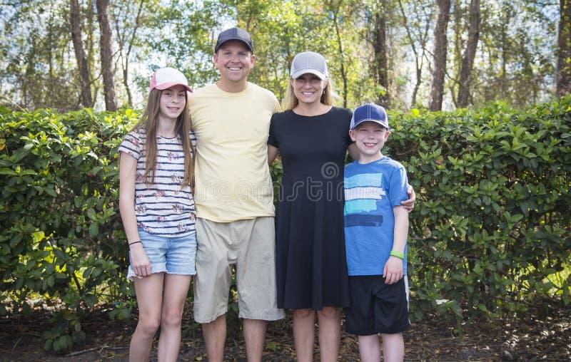 Χαριτωμένη νέα οικογένεια όλες που φορούν τα καπέλα ή τα καλύμματα μπέιζ-μπώλ στοκ φωτογραφία με δικαίωμα ελεύθερης χρήσης