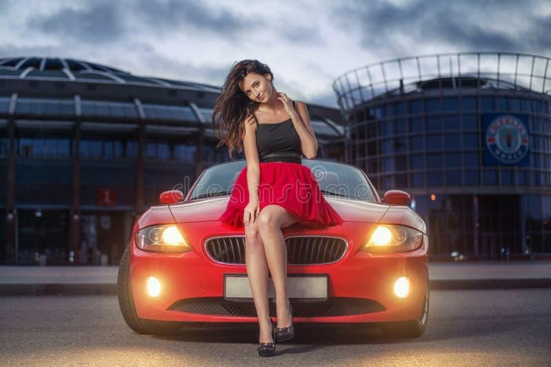 Χαριτωμένη νέα συνεδρίαση γυναικών brunette σε ένα καπό του κόκκινου αυτοκινήτου καμπριολέ πολυτέλειας στο ηλιοβασίλεμα στοκ εικόνες