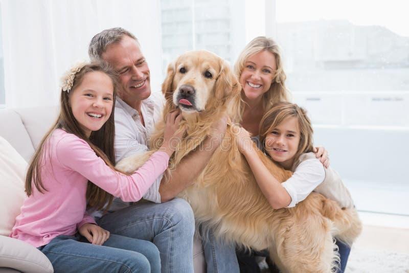 Χαριτωμένη οικογένεια που χρυσό retriever τους στον καναπέ στοκ φωτογραφίες με δικαίωμα ελεύθερης χρήσης