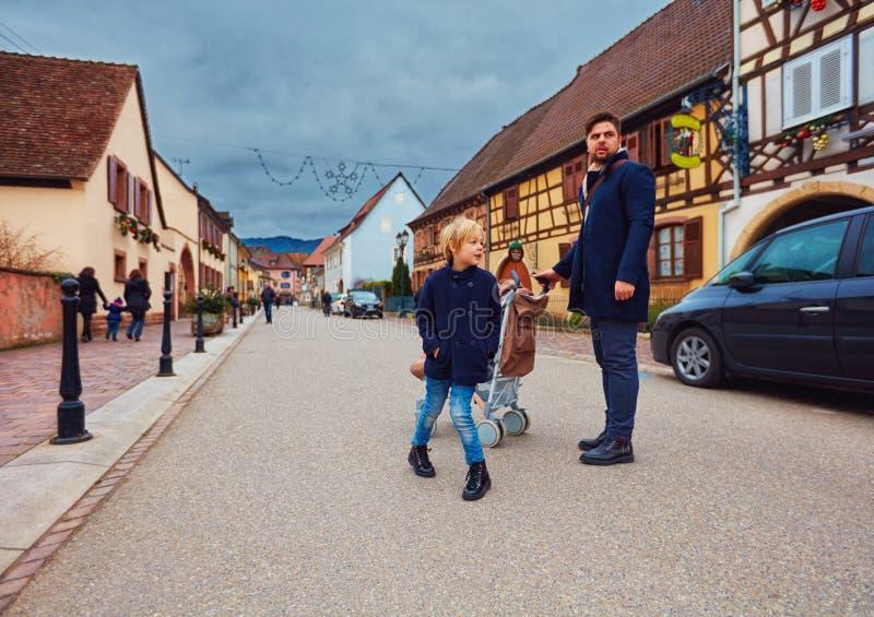 Χαριτωμένη οικογένεια, τουρίστες στην οδό του χωριού Eguisheim, Γαλλία στοκ εικόνα