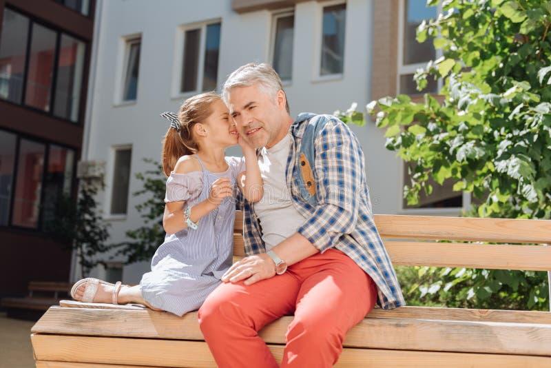 Χαριτωμένη συμπαθητική συνεδρίαση κοριτσιών με τον πατέρα της στον πάγκο στοκ εικόνες