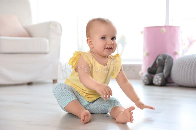 Χαριτωμένη συνεδρίαση κοριτσάκι στο πάτωμα στοκ εικόνα
