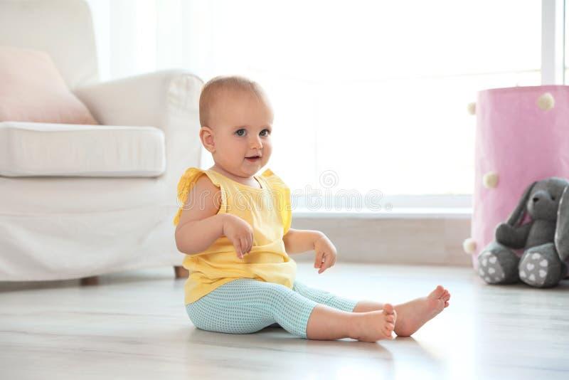 Χαριτωμένη συνεδρίαση κοριτσάκι στο πάτωμα στοκ εικόνες με δικαίωμα ελεύθερης χρήσης