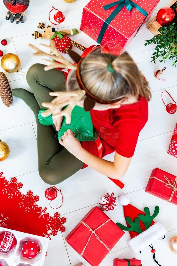 Χαριτωμένη συνεδρίαση κοριτσιών στο ανοίγοντας χριστουγεννιάτικο δώρο πατωμάτων, τοπ άποψη στοκ εικόνα