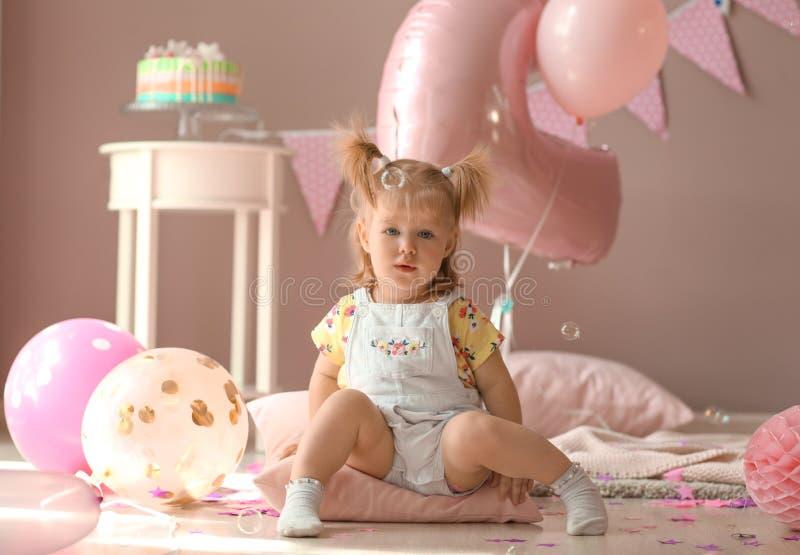 Χαριτωμένη συνεδρίαση μικρών κοριτσιών στο μαξιλάρι στο δωμάτιο που διακοσμείται για τη γιορτή γενεθλίων στοκ φωτογραφία