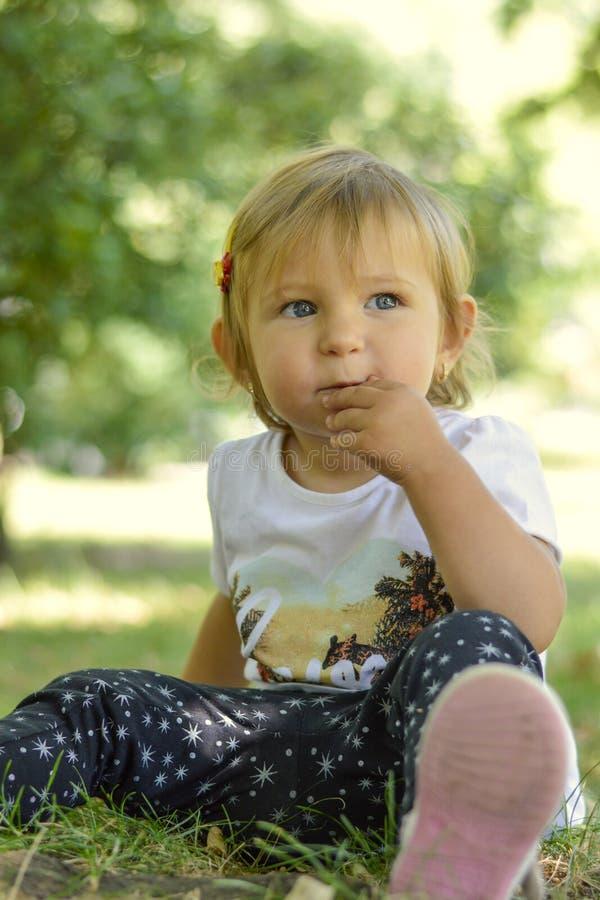 Χαριτωμένη συνεδρίαση κοριτσάκι ενός έτους βρεφών στη χλόη στο πάρκο στοκ εικόνα με δικαίωμα ελεύθερης χρήσης
