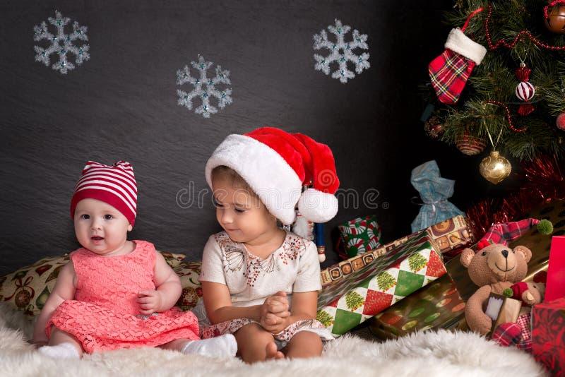 Χαριτωμένη συνεδρίαση κοριτσάκι στην κουβέρτα στο εσωτερικό Χριστουγέννων στοκ φωτογραφίες