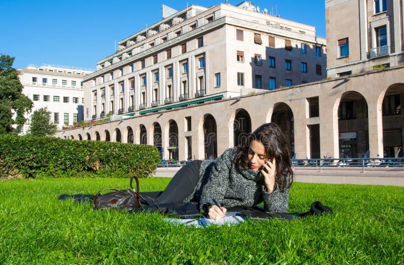 Χαριτωμένη συνεδρίαση κοριτσιών στην πράσινη χλόη που μιλά στο τηλέφωνο και που γράφει κάτι με την ταμπλέτα και τα σημειωματάρια στοκ εικόνες με δικαίωμα ελεύθερης χρήσης