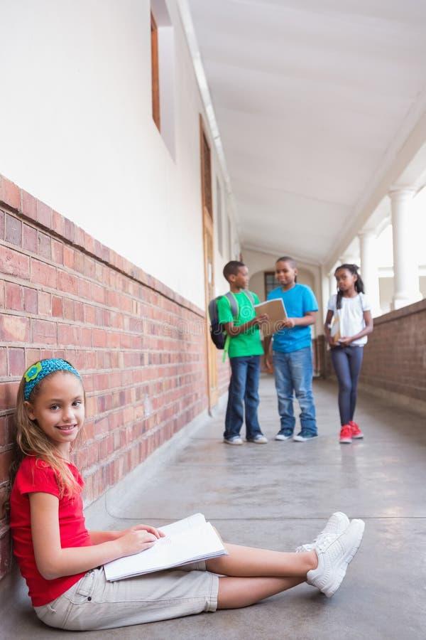 Χαριτωμένη συνεδρίαση μαθητών στο έδαφος που χαμογελά στη κάμερα στοκ φωτογραφία με δικαίωμα ελεύθερης χρήσης