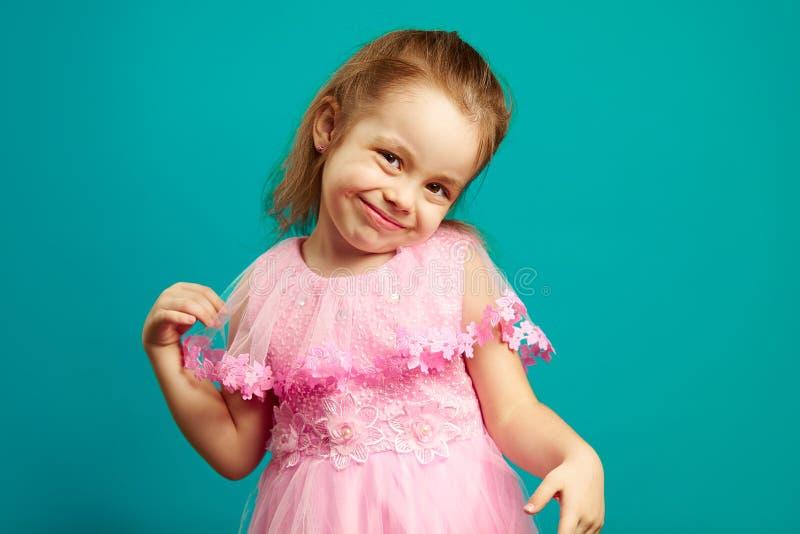Χαριτωμένη τοποθέτηση μικρών κοριτσιών απομονωμένη φορεμάτων μπροστά στο μπλε στοκ εικόνα