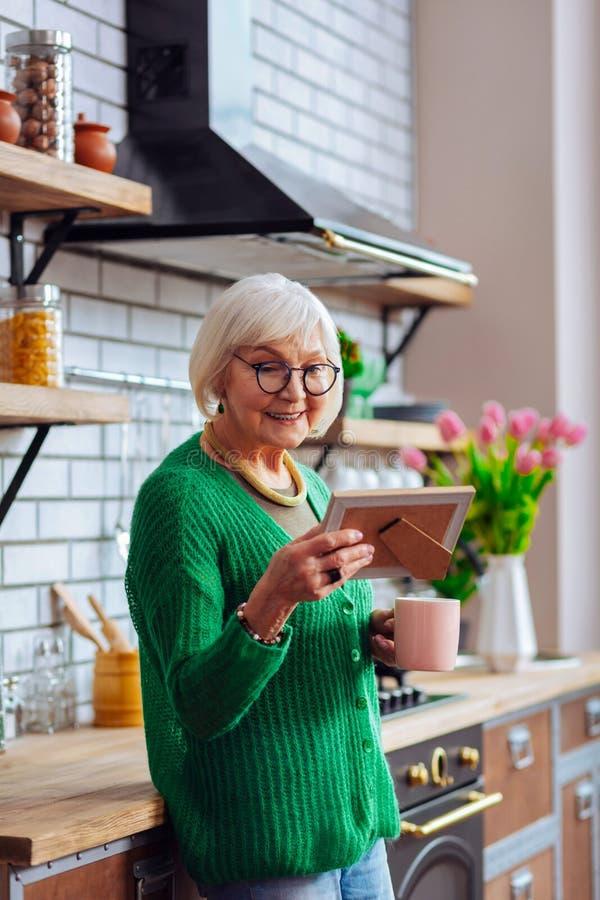 Χαριτωμένη φωτογραφία θαυμασμού κυρίας στο πλαίσιο και κράτημα του καφέ πρωινού στοκ εικόνα