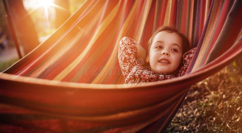 Χαριτωμένη χαλάρωση μικρών κοριτσιών σε μια αιώρα στοκ εικόνες