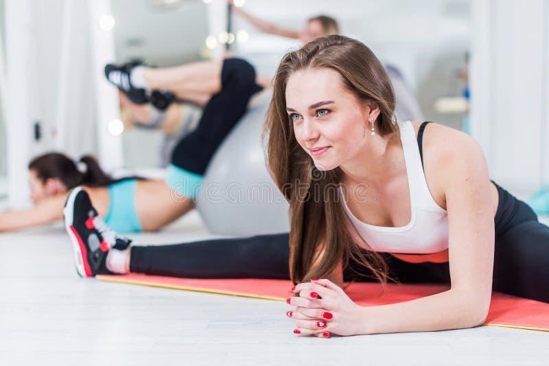 Χαριτωμένη χαμογελώντας νέα κυρία sportswear που κάνει την προηγμένη μέση διασπασμένη άσκηση που κάμπτει πέρα από την κλίση στα ό στοκ φωτογραφίες με δικαίωμα ελεύθερης χρήσης