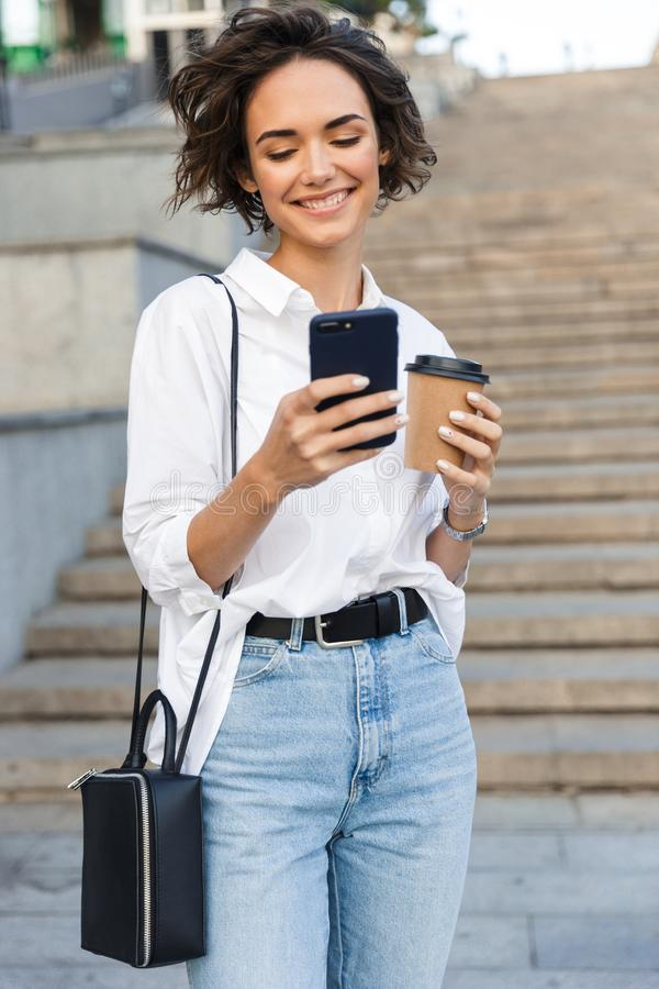 Χαριτωμένη όμορφη γυναίκα που περπατά στην οδό που χρησιμοποιεί τον κινητό καφέ τηλεφωνικής εκμετάλλευσης στοκ φωτογραφία με δικαίωμα ελεύθερης χρήσης