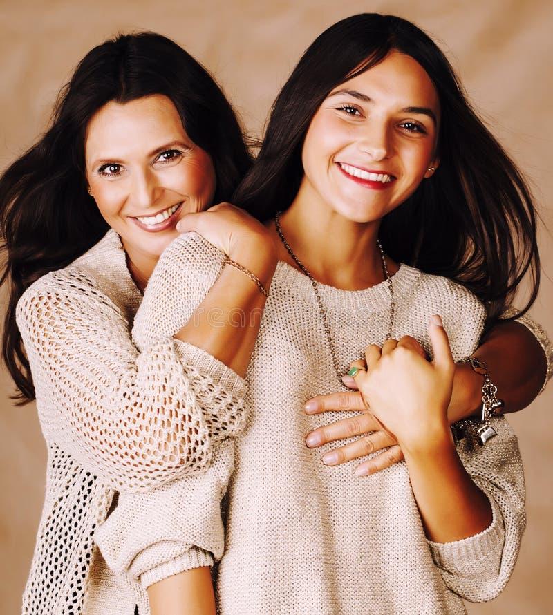 Χαριτωμένη όμορφη κόρη εφήβων με την ώριμη μητέρα που αγκαλιάζει, στενοί επάνω tann μιγάδες brunette ύφους μόδας makeup από κοινο στοκ εικόνες