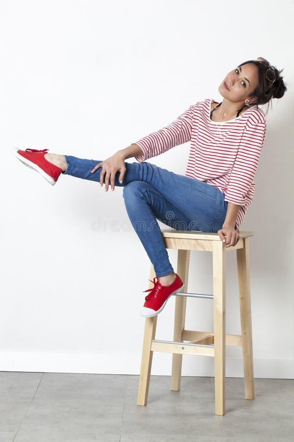 Χαριτωμένη όμορφη νέα γυναίκα με την προκλητική τοποθέτηση που τεντώνει ένα πόδι στοκ φωτογραφίες
