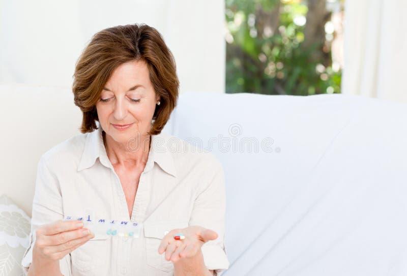 Χαριτωμένη ώριμη γυναίκα με τα χάπια στοκ εικόνες
