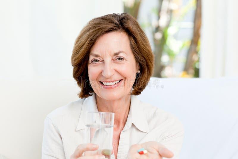 Χαριτωμένη ώριμη γυναίκα με τα χάπια στοκ φωτογραφίες με δικαίωμα ελεύθερης χρήσης
