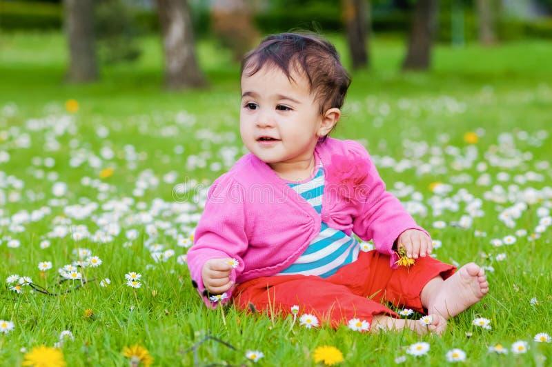 Χαριτωμένη chubby συνεδρίαση μικρών παιδιών στη χλόη που χαμογελά ερευνώντας τη φύση υπαίθρια στο πάρκο στοκ φωτογραφία