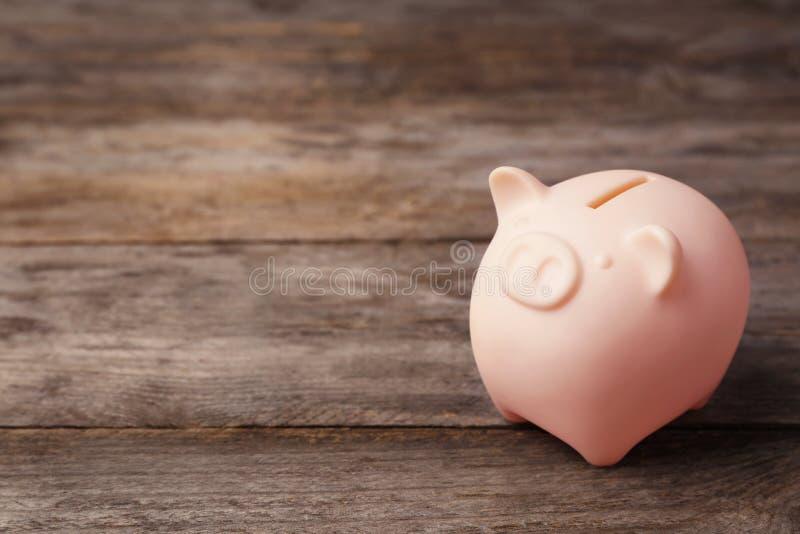 Χαριτωμένη piggy τράπεζα στον ξύλινο πίνακα στοκ φωτογραφία με δικαίωμα ελεύθερης χρήσης