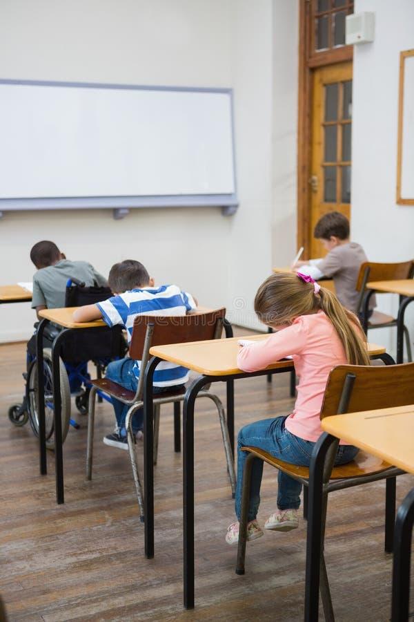 Χαριτωμένοι μαθητές που γράφουν στα γραφεία στην τάξη στοκ εικόνες