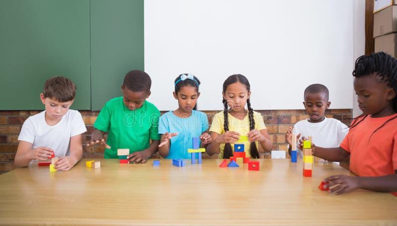 Χαριτωμένοι μαθητές που παίζουν με τις δομικές μονάδες στοκ εικόνα