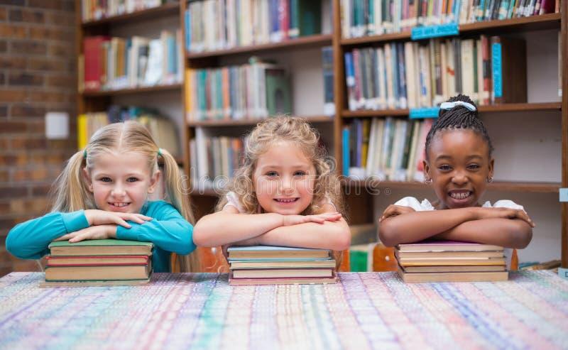 Χαριτωμένοι μαθητές που χαμογελούν στη κάμερα στη βιβλιοθήκη στοκ εικόνες