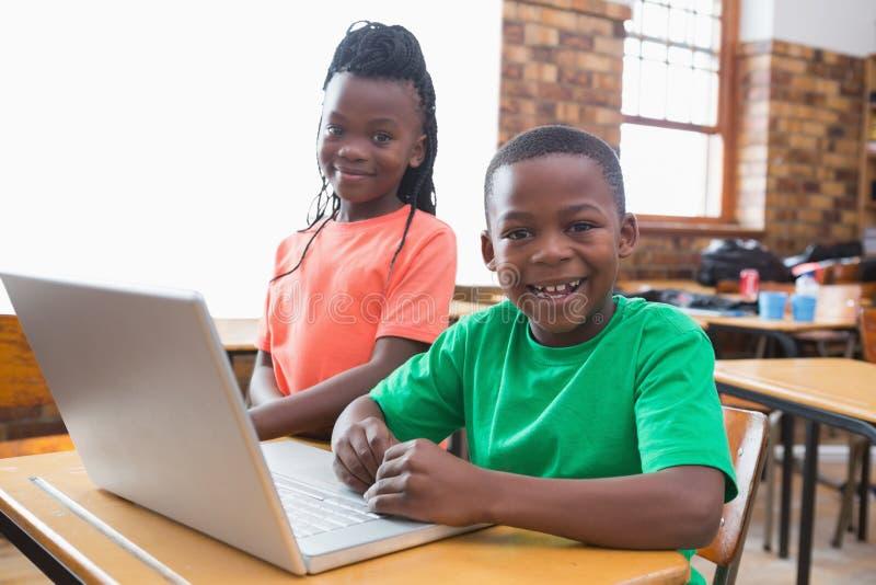 Χαριτωμένοι μαθητές που χρησιμοποιούν το lap-top στην τάξη στοκ εικόνες