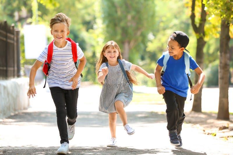 Χαριτωμένοι μικροί μαθητές που τρέχουν υπαίθρια στοκ φωτογραφίες με δικαίωμα ελεύθερης χρήσης