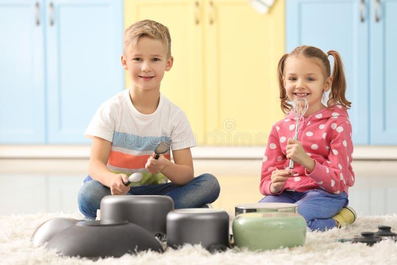 Χαριτωμένοι μικροί μουσικοί που παίζουν τα τύμπανα στο σκεύος για την κουζίνα στοκ φωτογραφία