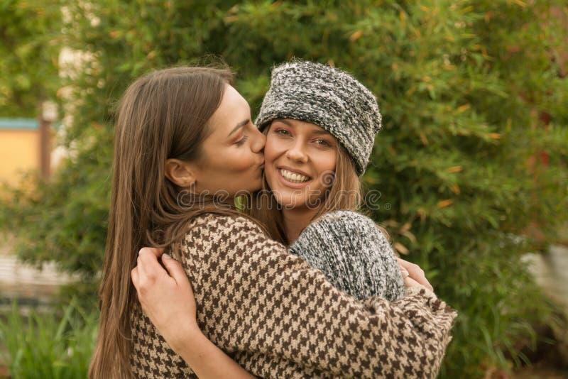 Χαριτωμένοι δύο νέοι ενήλικοι γυναίκες, κεφάλι και πυροβολισμός ώμων, μάγουλο φιλιών, στοκ εικόνες με δικαίωμα ελεύθερης χρήσης