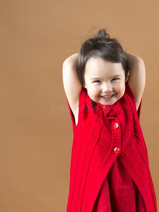 Χαριτωμένος λίγη ευτυχής τοποθέτηση κοριτσιών σε ένα κόκκινο φόρεμα στοκ εικόνα με δικαίωμα ελεύθερης χρήσης