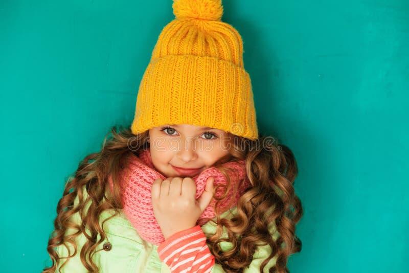 Χαριτωμένος λίγη κυρία που φορά την κίτρινη μάλλινη ΚΑΠ και το θερμό μαντίλι στοκ εικόνες με δικαίωμα ελεύθερης χρήσης