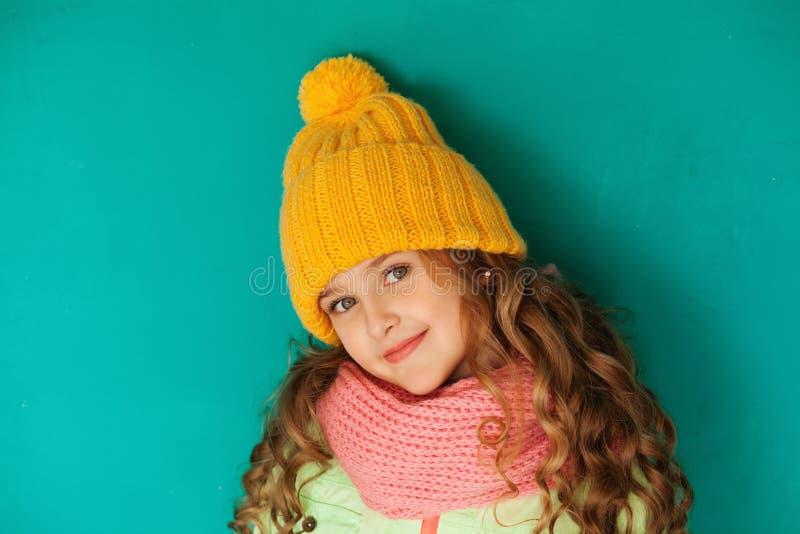 Χαριτωμένος λίγη κυρία που φορά την κίτρινη μάλλινη ΚΑΠ και το θερμό μαντίλι στοκ φωτογραφία