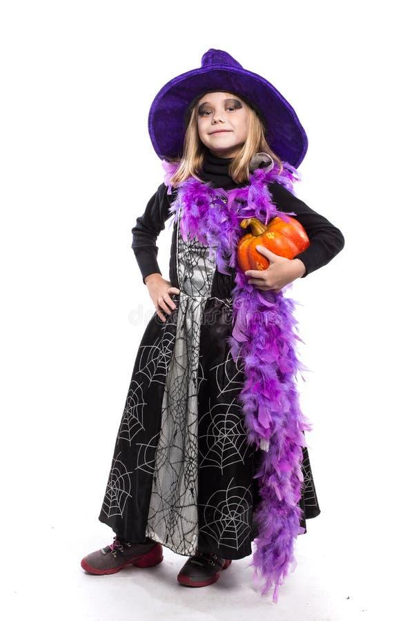 Χαριτωμένος λίγη μάγισσα αποκριών που κρατά μια πορτοκαλιά κολοκύθα στοκ φωτογραφία με δικαίωμα ελεύθερης χρήσης