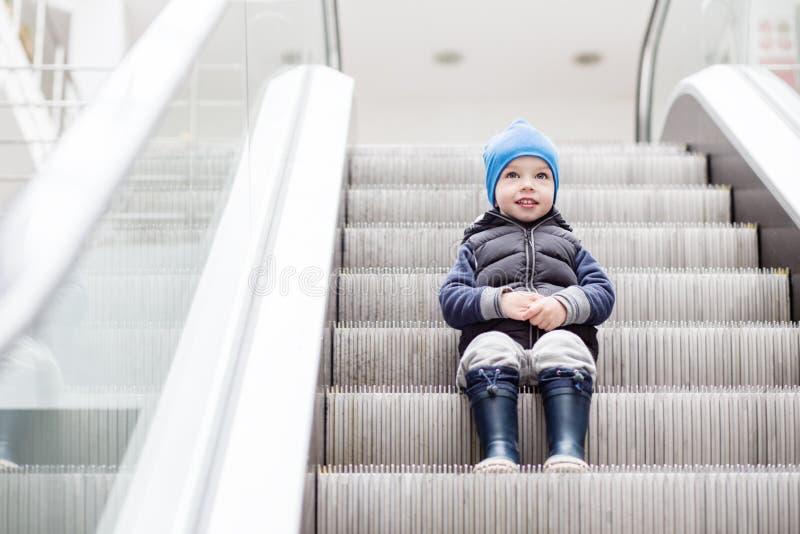 Χαριτωμένος λίγη συνεδρίαση παιδιών στην κίνηση της σκάλας στοκ εικόνες