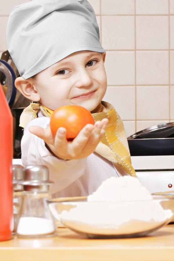Χαριτωμένος λίγος μάγειρας που δίνει την ντομάτα στοκ φωτογραφίες με δικαίωμα ελεύθερης χρήσης